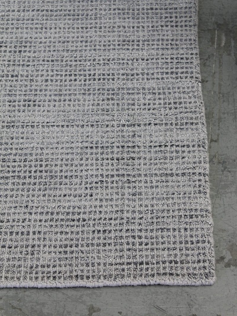 The Homer Grey rug is an elegant handloom knotted wool and artsilk rug, with a textured grid design and beautifully soft finish.