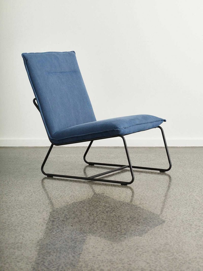 Tyler Occasional Chair in Indigo Blue. Fully upholstered armless occasional chair with powdercoated black metal base. Upholstered seat in stonewashed fabric.