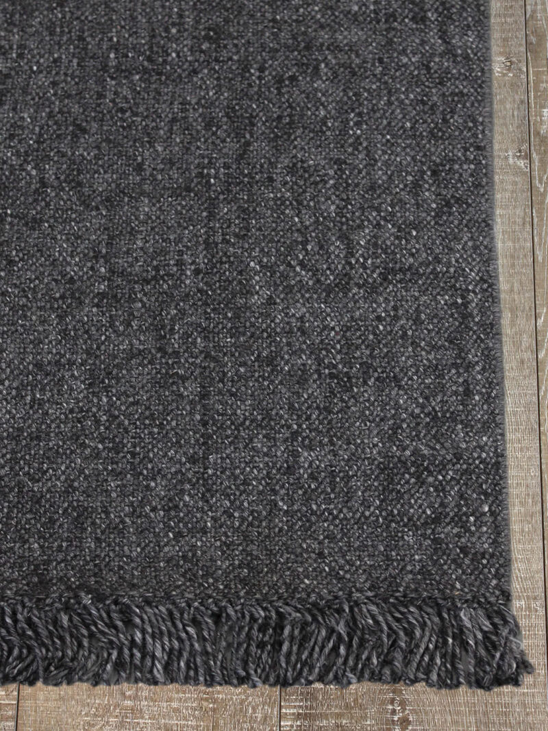 Positano handwoven wool rug with fringe in Dark Grey - corner image