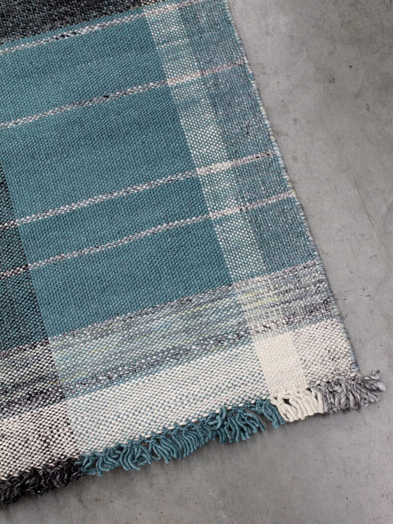 Trieste Teal rug with check design in shades of grey and blue/green, handwoven in 100% wool with fringing.